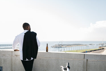 Spain, Barcelona, businessman with bottle of beer looking at view - JRFF00935