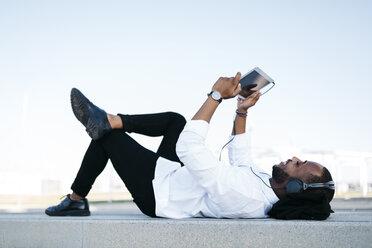 Smiling man lying on the floor wearing headphones looking at tablet - JRFF00941
