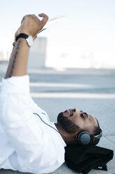 Man lying on the floor wearing headphones looking at tablet - JRFF00944