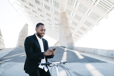 Smiling businessman on bicycle looking at cell phone - JRFF00947