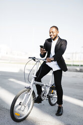 Smiling businessman with bicycle looking at cell phone - JRFF00950