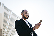 Smiling businessman looking at cell phone - JRFF00953