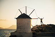 Greece, Amorgos, Aegialis, man with raised arms standing besides wind mill at sunset - GEMF01145