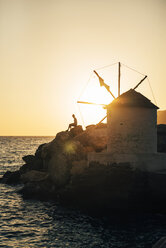Greece, Amorgos, Aegialis, silhouette of man sitting near wind mill at sunset - GEMF01148