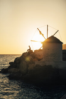 Greece, Amorgos, Aegialis, silhouette of man sitting near wind mill at sunset - GEMF01148