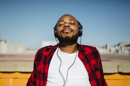 Man listening to music with headphones outside - JRFF00957