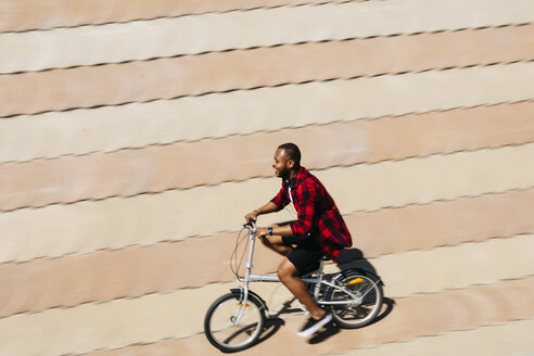 Smiling man riding bicycle - JRFF00969