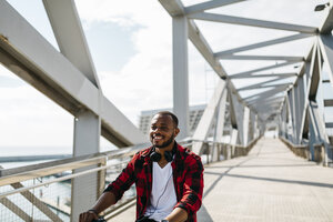Smiling man riding bicycle on a bridge - JRFF00972