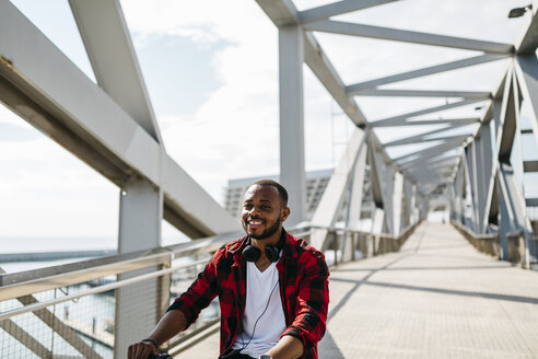 Smiling man riding bicycle on a bridge - JRFF00972