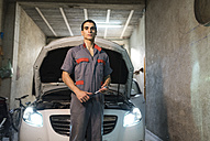 Portrait of mechanic in front of car in a garage - JASF01235