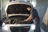Mechanic repairing car in a garage - JASF01238