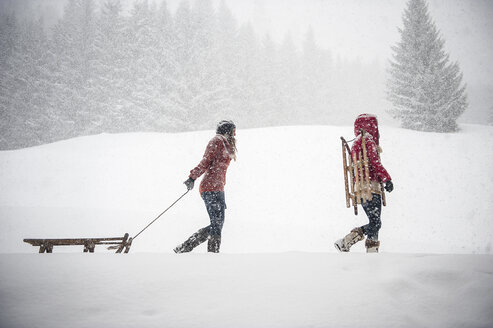 Two young women with sledges in heavy snowfall - HHF05411