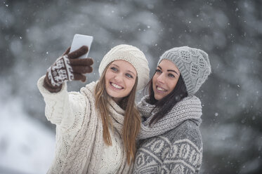Two young women taking a selfie in snowfall - HHF05417