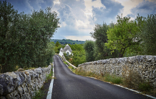 Italy, Apulia, Country road and trullo behind stone wall and olive trees - DIKF00215