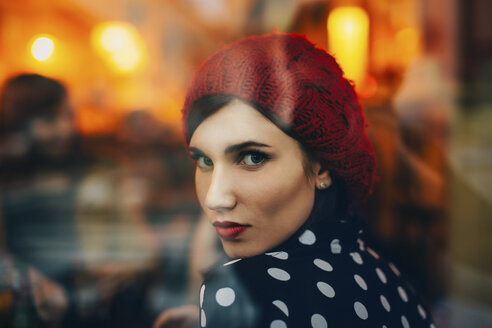 Portrait of young woman wearing red hat looking through window of a pub in the evening - LCUF00057