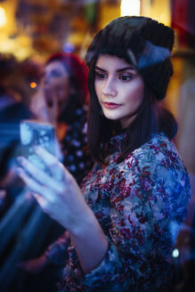 Portrait of young woman with smartphone behind windowpane of a pub in the evening - LCUF00063