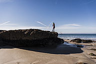 France, Crozon peninsula, teenage girl standing on rock at the beach - UUF08647