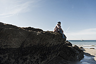 France, Crozon peninsula, teenage girl sitting on rock at the beach - UUF08650