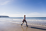 France, Crozon peninsula, teenage girl walking on the beach - UUF08656