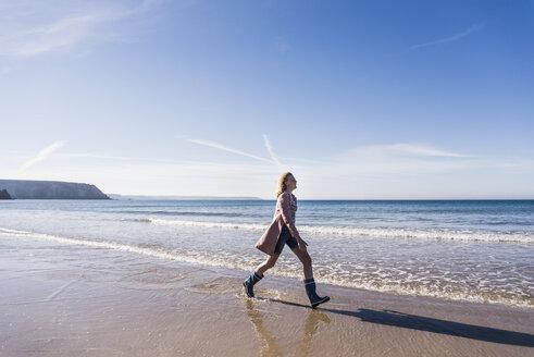 France, Crozon peninsula, teenage girl walking on the beach - UUF08656