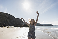 France, Crozon peninsula, happy teenage girl with raised arms on the beach - UUF08662