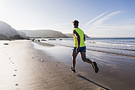 France, Crozon peninsula, young man running on the beach - UUF08677