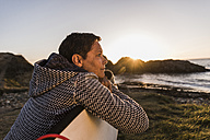France, Bretagne, Crozon peninsula, woman at the coast at sunset with surfboard - UUF08686