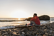 France, Bretagne, Crozon peninsula, woman sitting on stony beach at sunset with surfboard - UUF08689