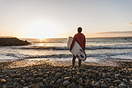 France, Bretagne, Crozon peninsula, woman standing on stony beach at sunset holding surfboard - UUF08692
