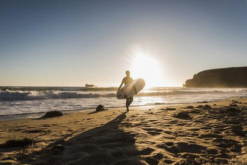 France, Bretagne, Crozon peninsula, woman walking on beach at sunset carrying surfboard - UUF08704