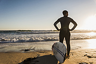 France, Bretagne, Crozon peninsula, woman standing on beach at sunset with surfboard - UUF08710