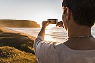France, Bretagne, Crozon peninsula, woman at the coast at sunset taking picture with tablet - UUF08719