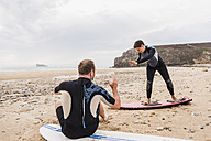 France, Bretagne, Crozon peninsula, man teaching woman surfing on beach - UUF08734