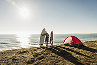 Young couple with surfboard camping at seaside - UUF08753