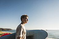 Teenage boy with surfboard looking to the sea - UUF08756