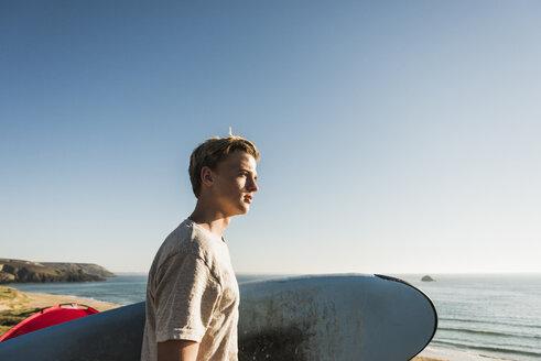 Teenage boy with surfboard looking to the sea - UUF08756