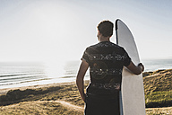 Back view of teenage boy with surfboard looking to the sea - UUF08759