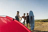 Three friends with surfboards camping at seaside - UUF08762