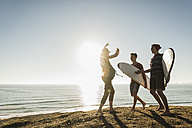 Three friends with surfboards camping at seaside - UUF08765