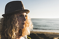 Portrait of blond teenage girl wearing hat on the beach at evening twilight - UUF08774