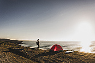Teenage girl with red tent and surfboard at seaside in the evening twilight - UUF08777