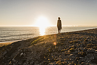 Back view of teenage girl standing on hill at sunset looking to the sea - UUF08795