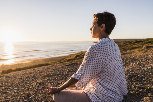 Woman meditating at seaside by sunset - UUF08801