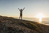 Woman with arms raised standing on hill at sunset looking to the sea - UUF08804
