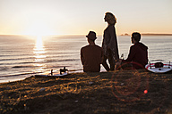 Three friends enjoying sunset on the beach - UUF08807