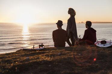Three friends enjoying sunset on the beach - UUF08807