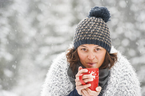 Portrait of woman wearing bobble hat holding cup with hot beverage in winter - HHF05426
