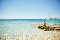 Greece, Koufonissi, Man sitting on rock looking at clear water of the Aegean Sea - GEMF01156