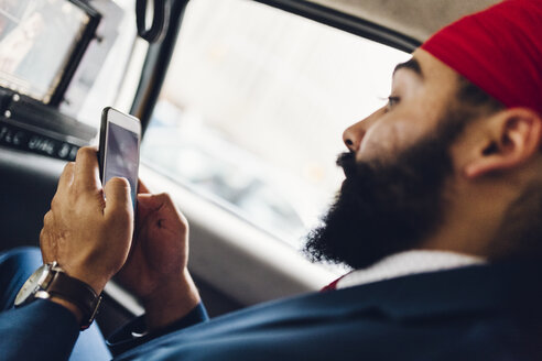 Indian businessman using smartphone in taxi - GIOF01527
