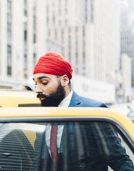 Indian businessman in Manhattan entering a yellow cab - GIOF01533